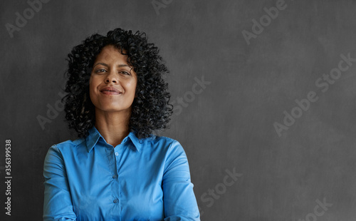 Smiling businesswoman standing by an office chalkboard Fototapete