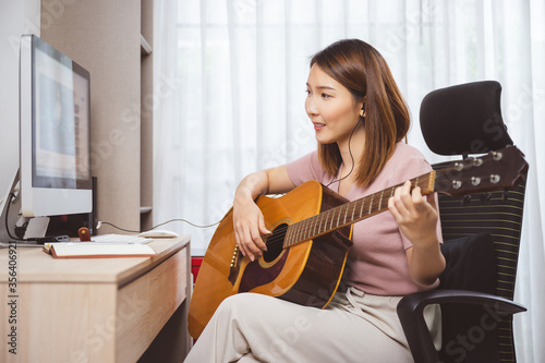 Asian woman guitar player and vlogger playing guitar in front computer at home while social distancing of coronavirus outbreak, online guitar lesson,livestream on social media concept Canvas Print