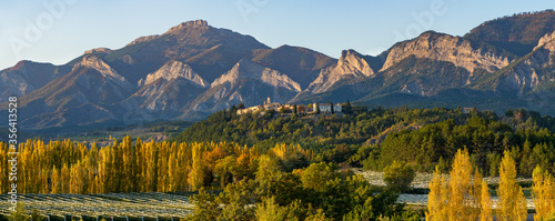 The hilltop village of Ventavon in Autumn with peuplar trees and orchards (panoramic). Durance Valley, Hautes-Alpes, European Alps, France