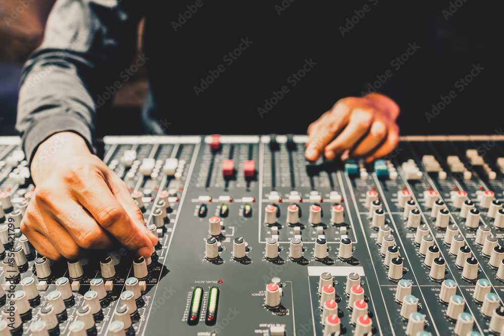 Fototapeta male producer, dj, sound engineer hands adjusting knob on audio mixing console