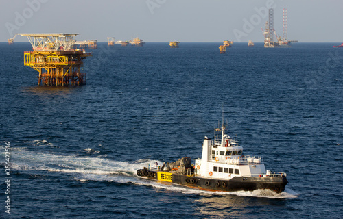 Fotografering Oil rigs and a transportation vessel in the South China Sea