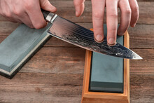 Man Sharpening A Chef's Knife With Damascus Steel