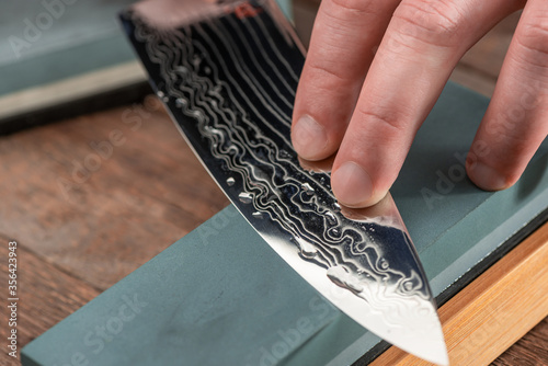 Papel de parede Close-up on a Damascus steel blade being sharpened with a whetstone