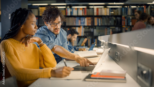 Photo University Library: Gifted Black Girl uses Laptop, Smart Classmate Explains and Helps Her with Class Assignment