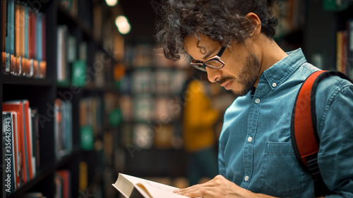 Photographie University Library: Talented Hispanic Boy Wearing Glasses Standing Next to Bookshelf Reads Book for His Class Assignment and Exam Preparations