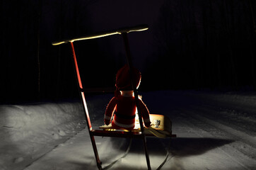 small santa travelling home on kicksled on snowy road with suitcase and lantern