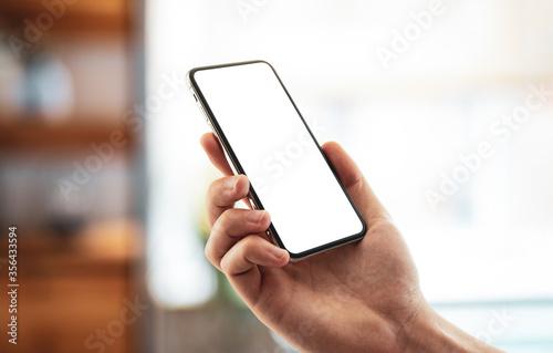 Foto Man using smartphone frameless mockup blank screen in home interior