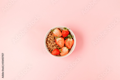 Fototapeta Breakfast bowls with granola, milk and organic tasty strawberries on pink background. horizontal space for text obraz