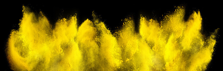 yellow holi paint color powder explosion isolated dark black background. industry beautiful party festival concept
