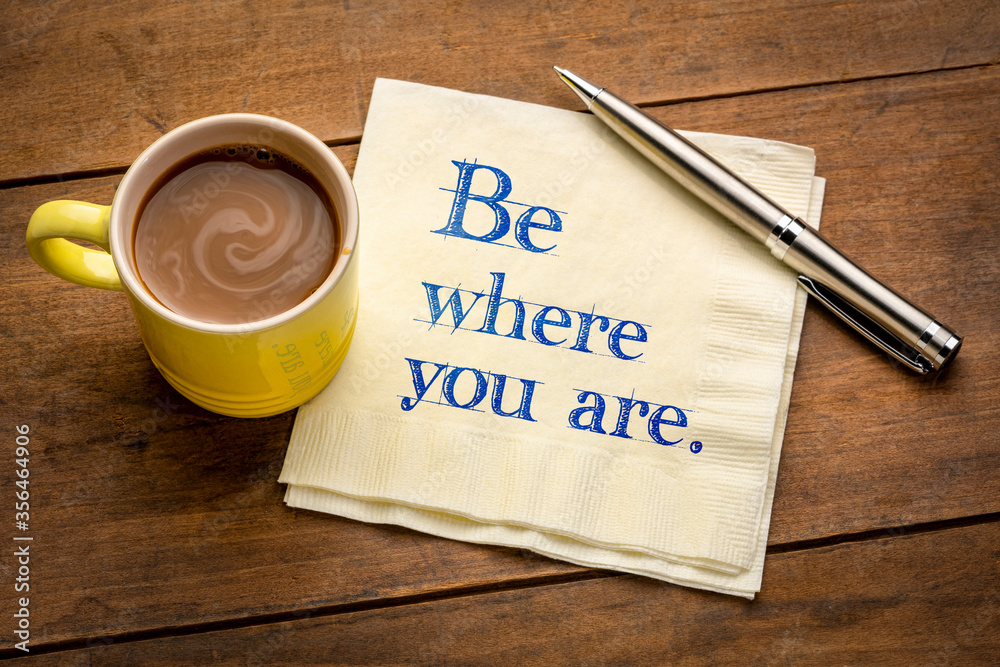 Fototapeta Be where you are  - inspirational handwriting on a napkin with a cup of coffee, be present in the moment reminder