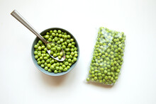 Green Peas In A Bowl And Transparent Plastic Package. Top View On White Background