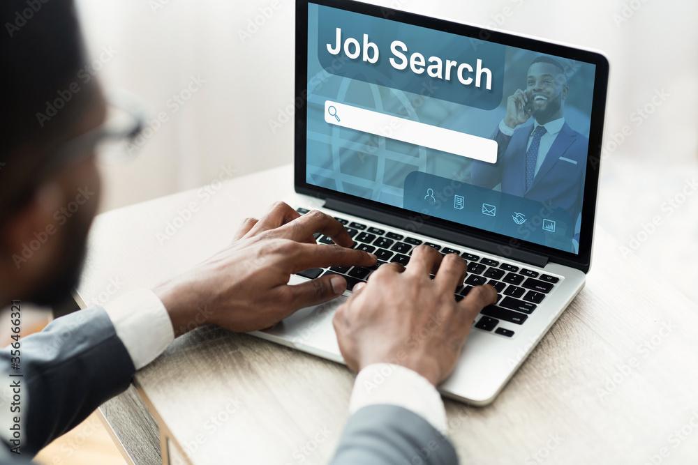 Fototapeta Black man using laptop with job search engine on screen