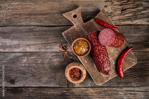 Fototapeta salami sausage on a old wooden table. farm organic food. Food recipe background. space for text. top view obraz