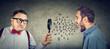 Leinwandbild Motiv Curious businessman looking through a magnifying glass at an angry screaming man