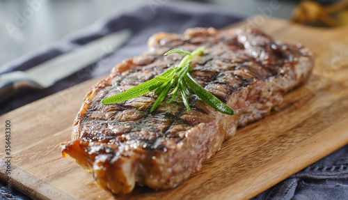 Leinwand Poster grilled new york strip steak resting on wooden cutting board with rosemary garni