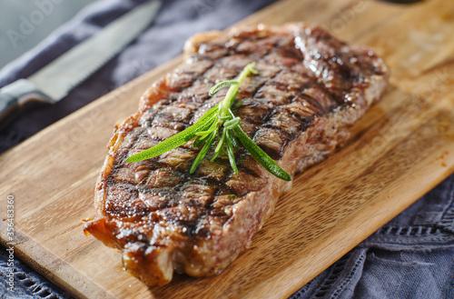 Fototapeta grilled new york strip steak resting on wooden cutting board with rosemary garnish obraz