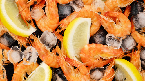 Photo fresh shrimps with lemon and ice cubes  closeup.  macro shot