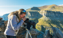 Blonde Woman At Ordesa National Park Looking Thought A Telescope On A Tripod Some Details Of The Park. Behind The Woman There Are Some Peaks And Rocks Of The Panoramic View. Horizontal Photo