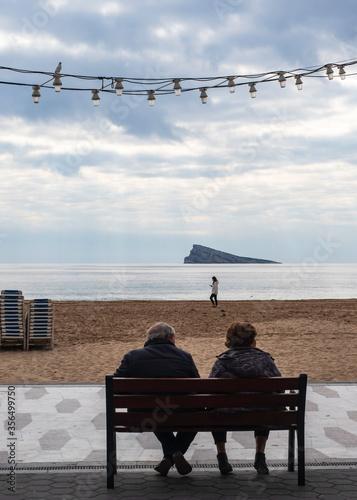 Pareja de jubilados sentados en el paseo marítimo de Benidorm disfrutando del pa Canvas Print
