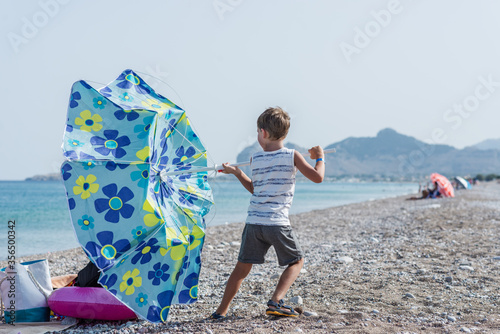 Fotografie, Obraz Toddler boy standing on windy beach