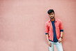 Portrait of young stylish indian man model isolated on pink wall background.