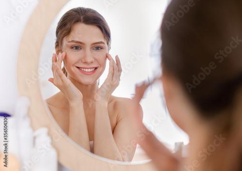 Photo Beautiful woman looking at mirror and applying eye serum