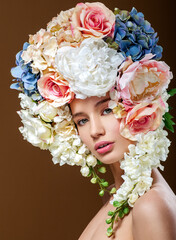 Fototapeta Do Spa Beautiful woman with flowers in her hair. Bouquet of Beautiful Flowers. Hairstyle with flowers. Nature Hairstyle.