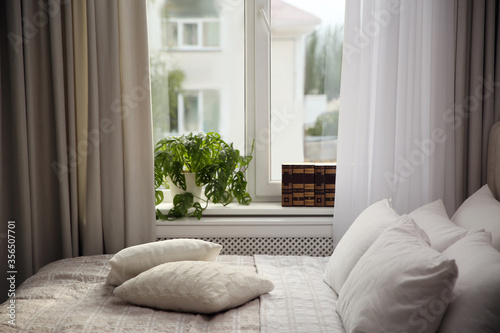 Fényképezés Comfortable bed with pillows and blanket near window