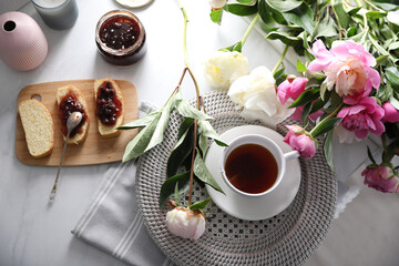 Beautiful peonies and breakfast on marble table, flat lay