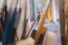 Many Paintbrushes In Glass On ...