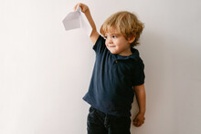 Cute Blond Boy In Casual Outfit Playing With Paper Plane Smiling Brightly At Camera On White Wall Background