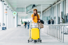 Smiling Lady In Casual Outfit And Headphones With Leather Jacket Bag And Passport In Hand Looking At Camera And Carrying Luggage Cart Near Modern Airport Building
