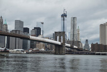 From Below Of Manhattan Bridge Seen From River Bank With City Buildings And Cloudy Gray Sky In Background In New York City