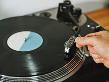From Above Cropped Person Hands Adjusting A Contemporary Vinyl Record Player With Retro Disc Placed On Wooden Table