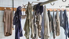 Carelessly Scattered Dirty Miners Uniforms Hanging On Hooks In Locker Room With White Walls Tiled In Abandoned Coal Mine
