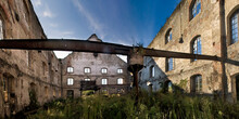 Low Angle Of Weathered Stone Walls Of Old Industrial Building With Latticed Windows And Overgrown Ground Against Blue Sky In Sunny Day In Asturias In Spain