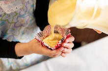 Cropped Unrecognizable Kid Hands Holding Paper Cup While Adult Pours Batter Cupcake Mix In A Jar At Home