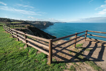 Picturesque Landscape Of Seashore With Wooden Fence And Green Field Against Cloudy Blue Sky In Sunny Summer Day In Countryside