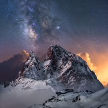 Amazing View Of White Snowy Mountain Range Under Incredible Night Starry Sky With Breaking Rays Of Rising Sun From Behind Mountains In Winter Evening