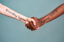 Handshake Between Black And White Human Woman And Male Hands With The Message Text Standing Together Against HATE. Concept Of Black Lives Matter Protest Against Racism And Police Brutality.