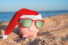 Toy Piggy Bank In Form Of Pink Pig In Sunglasses With Polarizing Lenses And Christmas Santa Hat Is Standing On Sandy Beach On Sunny Day, Symbols Of Years Of The Eastern Calendar, Chinese Zodiac