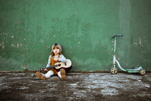 Little Girl With Ukulele Sitting On Rough Ground Near Kick Scooter Against Weathered Green Wall On Street