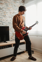Full Body Adult Man Playing Electric Guitar While Standing In Cozy Room At Home