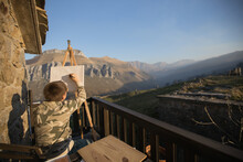 Back View Of Faceless Boy Sitting At Easel On Picturesque Veranda Of Country House And Drawing Picture In Cantabria