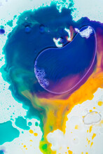 Backdrop With Top View Of Abstract Vivid Blue And Orange Inky Circles Placed On Blurred Multicolored Transparent Surface