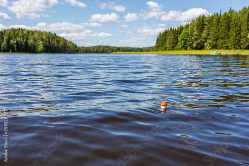 Fototapeta Beautiful landscape of the lake and the bobber on foreground, Finland