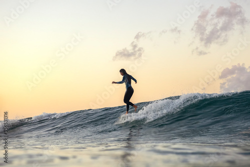Billede på lærred Surfer girl at sunset, Byron Bay Australia