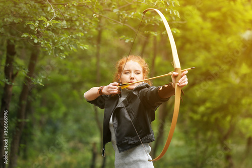 Fotografia Sporty young woman practicing archery outdoors