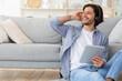 Joyful man listening to music, sitting on floor at home