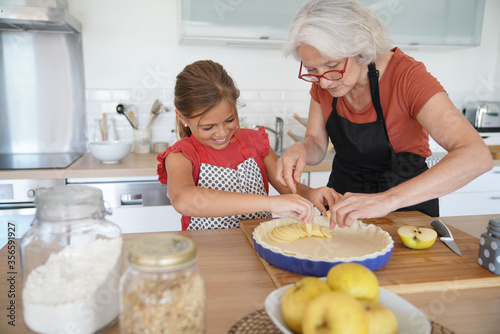 Photo Grandmother with grandkid making apple pie